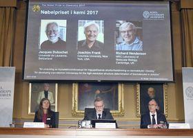 ノーベル化学賞の発表会場に映し出された(左から)ジャック・デュボシェ氏、ヨアヒム・フランク氏、リチャード・ヘンダーソン氏=4日、ストックホルム(AP=共同)