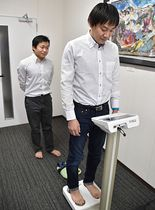 オフィスに設置された体組成計で体重を量る社員