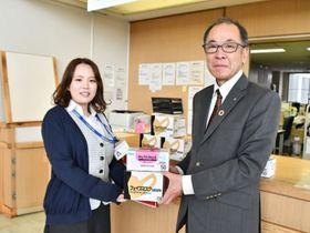 県立宮古病院の関係者に寄贈するマスクを手渡す石原弘村長(右)