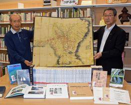 つがる市立図書館に農業水利などに関する郷土資料・図書を寄贈した笹森さん(左)と、同図書館の葛西〓輔館長※〓は「山」へんに「甚」