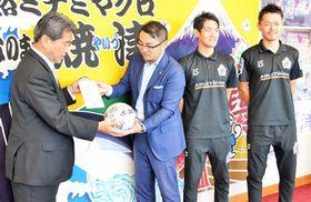 中野市長(左)に目録と選手のサインボールを手渡す新間社長=焼津市役所