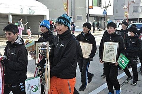 トロフィーや賞状を手に飯山市街地を練り歩く飯山高校スキー部の部員ら