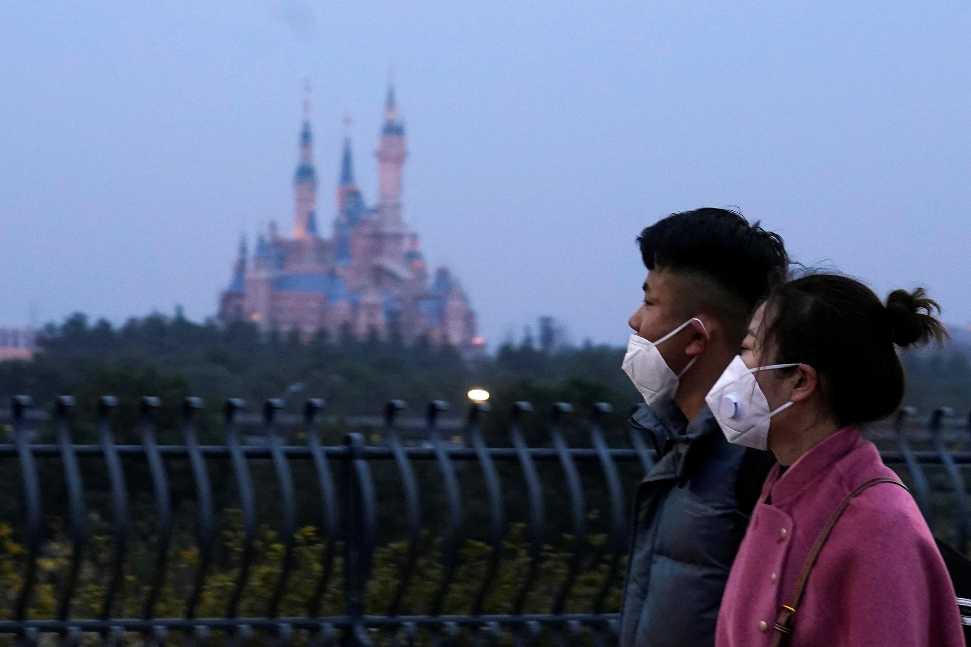 1月24日、中国・上海ディズニーランド付近を歩く訪問客(ロイター=共同)