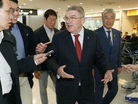 2018年11月、成田空港で取材に応じるIOCのバッハ会長(中央)と、出迎えたJOCの竹田恒和会長(右端)