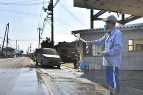 道路に水をまく安田明夫さん=15日午後3時35分=岡山県倉敷市真備町地区