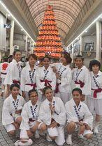 「いいっちゃ戸畑ヨイトサまつり」に初めて参加した日本ウェルネススポーツ大学北九州サテライトキャンパスの留学生。後列左端と右端は職員