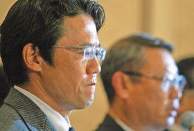 スト突入を決め、会見で険しい表情を見せる日本プロ野球選手会の古田会長(左)。右は経営者側の交渉役だった瀬戸山ロッテ球団代表=2004年9月17日、東京都内のホテルで