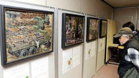 被爆者の証言を基に、基町高生徒が描いた作品に見入る来場者