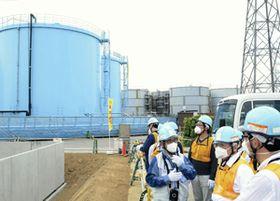 トリチウム水が保管されたタンク群を視察する小委員会の山本委員長(右から2人目)ら=15日午後、福島第1原発
