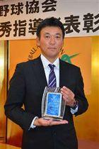 優秀指導者賞の表彰盾を手にする中泉監督