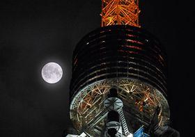 東京タワーの奥に浮かび上がる「中秋の名月」=24日午後10時18分、東京都港区