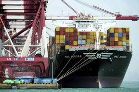 コンテナを搭載し、山東省青島を出航する大型貨物船=4月、青島(AP=共同)