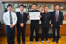 【21世紀枠の推薦校に選ばれた野球部キャプテンの植中君(中央)、川邊監督(左から2人目)ら=木本高で】