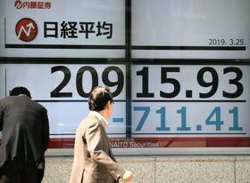 下げ幅が一時700円を超えた日経平均株価を示すボード=25日午前、東京都中央区