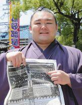 大相撲名古屋場所の番付表を手に笑顔を見せる東前頭筆頭の朝乃山=24日、愛知県蟹江町で