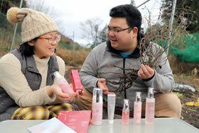 紫草を育てる農地で、収穫した根を持つ前川さん(右)と化粧品を手にするあやのさん=東近江市君ケ畑町