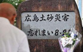 梅林小にある慰霊碑前で手を合わせる追悼献花式の参列者=20日午前9時26分、広島市安佐南区(撮影・天畠智則)