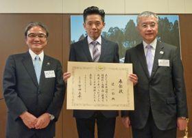 文化庁の宮田長官(左)から国際芸術部門の表彰を受け、記念撮影に応じる辻一弘さん(中央)=23日午後、文化庁