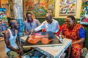 工房でティンガティンガの娘マルティナらと集う長老格アブダル・アモンデ・ムクーラ(中央右)。互いの技を盗みながら笑いの中で作業を進める=ダルエスサラーム(撮影・中野智明 共同)
