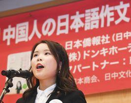 「中国人の日本語作文コンクール」の表彰式で、作品を発表する黄安キさん=12日、北京の日本大使館(共同)