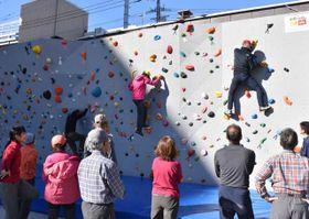 高さ5メートルのボルダリング用の壁を登る参加者