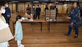 【内覧会の参加者におわせマルシェについて説明する小倉さん(右)=尾鷲市向井で】