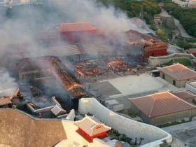 夜明けを迎えた首里城の火災現場。正殿(中央)は完全に崩落している