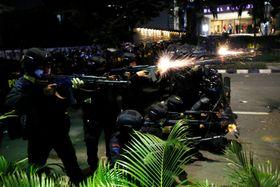 インドネシア・ジャカルタで、集団と衝突し、武器を使用する警察の部隊=22日(ロイター=共同)
