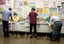 シールド越しに対応する住民検診の受付。予約制のため行列はできない=8月、栃木県栃木市の栃木保健福祉センター