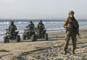 国境付近で、銃を手に警戒する米兵(右端)ら。メキシコ北西部ティフアナから撮影した=16日(共同)