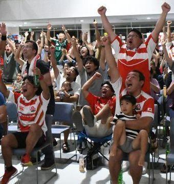日本代表のトライに総立ちで喜びを爆発させるパブリックビューイング会場の人々=13日、読谷村地域振興センター