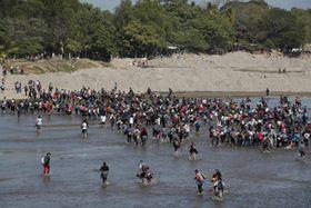 20日、グアテマラ南西部から、国境の川を渡りメキシコを目指す移民ら(AP=共同)