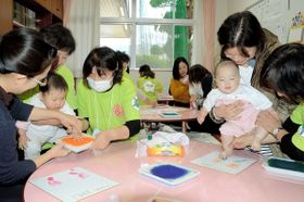赤ちゃんの成長の記念となる手形や足形を写し取る親子ら=観音寺市大野原町、ほっとはうす萩