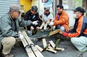 竹スキーの板を持ち、出来具合を確認する藤川さん(左から4人目)たち