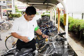 無施錠自転車に愛錠リングを貼付する警察官=24日午前、JR松山駅前