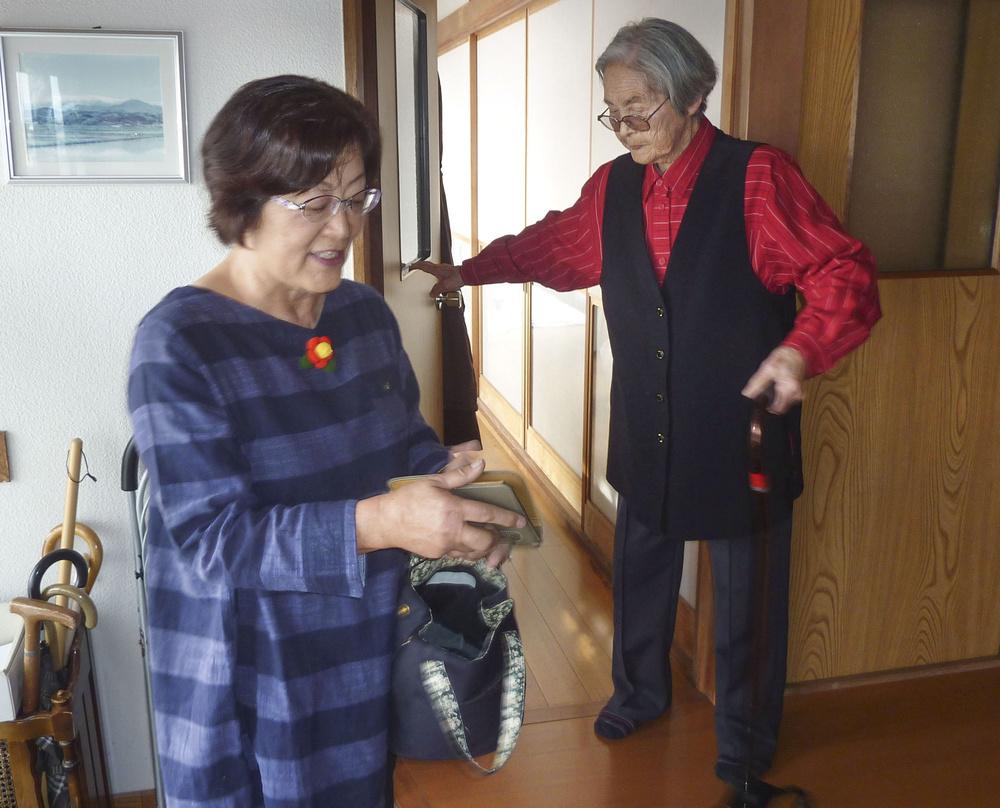 小畑きよ子(右)は週1回、生協のスタッフ高田洋子に財布やメモを渡して買い物を頼む