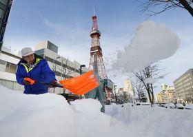 11月としては62年ぶりの大雪に見舞われた札幌市中心部で雪かきする男性。奥はさっぽろテレビ塔=2015年11月25日午後