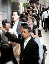 電車が止まり、長蛇の列ができたタクシー乗り場には外国人の姿も=18日夜、JR新大阪駅