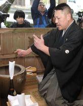 サンゾーロー祭で、亀の甲羅に炭火を押し当てる所作をする土脇さん=対馬市、雷神社