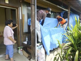 台風に備え、住民の求めに応じ家財道具にブルーシートをかぶせるボランティア=7月、愛媛県大洲市