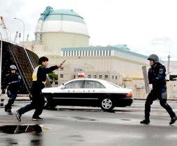 伊方原発のサイバー攻撃対処訓練で、犯人役(左から2人目)を取り押さえる県警機動隊員ら=18日午後、伊方町九町