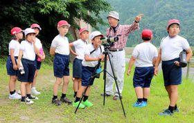 坂根さん(右から3人目)にブッポウソウの居場所を聞いて探す児童たち