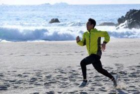 自主トレを公開し、打ち寄せる波を横目に砂浜を走る西武・秋山