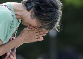 広島市の平和記念公園で原爆慰霊碑に手を合わせる女性