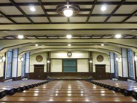 いすのクッションと天井板を除き、旧公衆衛生院時代の部材がそのまま残されている講堂=東京都港区