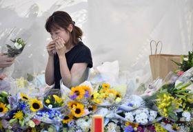 放火殺人事件が起きた「京都アニメーション」第1スタジオ近くの献花台で涙ぐむ女性。18日に発生から1カ月となる=17日午後、京都市伏見区