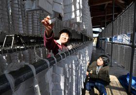 干し餅の仕上がり具合を確認する星野ケサさん(左)と菊池泰子さん=18日、遠野市松崎町