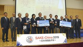 中国の一般消費者が好みの日本酒を選ぶ品評会で、授賞式に出席した蔵元関係者ら=23日、北京(共同)