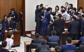 委員長席に野党委員が詰め寄る中、働き方改革関連法案が可決された衆院厚労委。左端は発言する加藤厚労相=25日午後