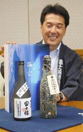 清信一・富士錦酒造社長と2本セットの「海と空」。「海中熟成」(右)は貯蔵中についたフジツボや貝が瓶を彩る=富士宮市役所で